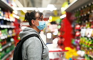 Selective focus color image depicting a caucasian woman in her 30s wearing a protective surgical face mask and plastic surgical gloves during the coronavirus (Covid-19) pandemic, in a bid to stop the spread of the virus. The woman is pushing her shopping cart inside a supermarket while shopping for groceries and fresh fruit and vegetables.