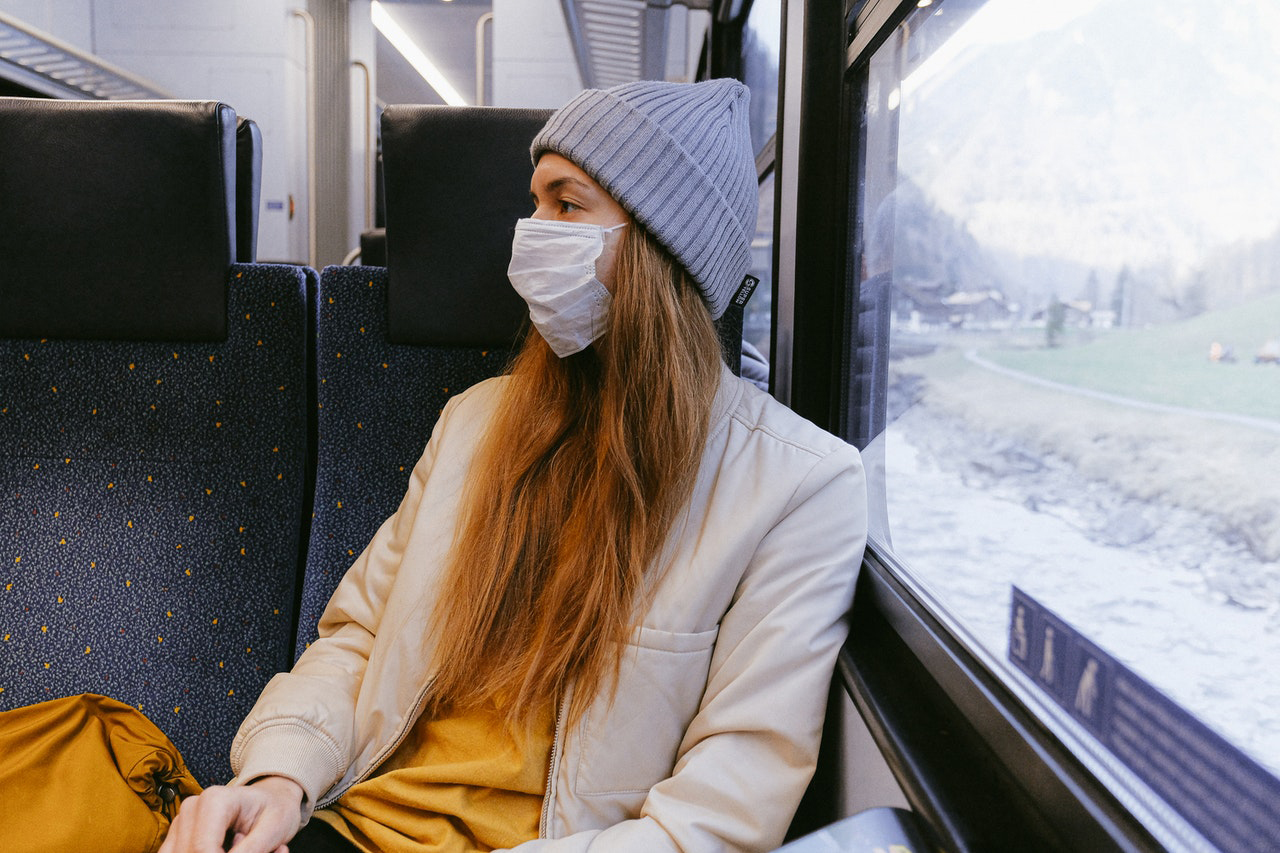 Girl with a mask on a train